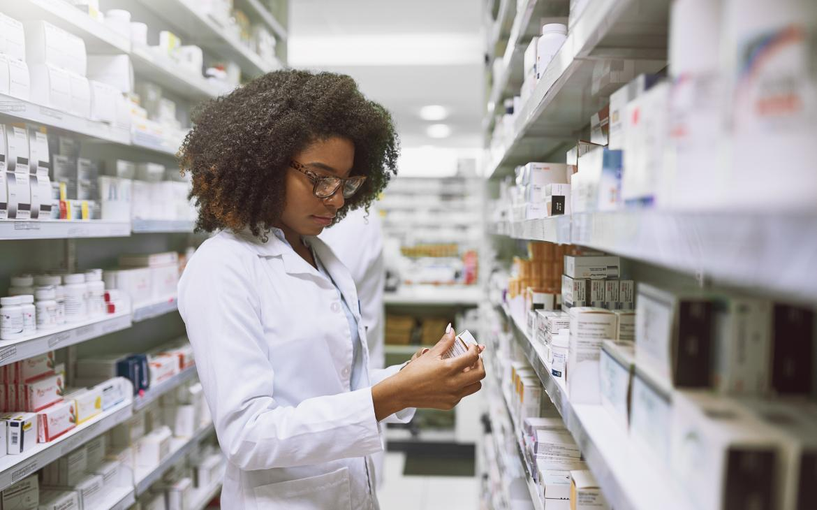 Pharmacist reads pill bottle